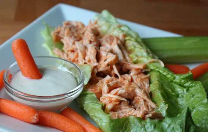 buffalo chicken shredded on a bed of lettuce with ranch and carrots on the side