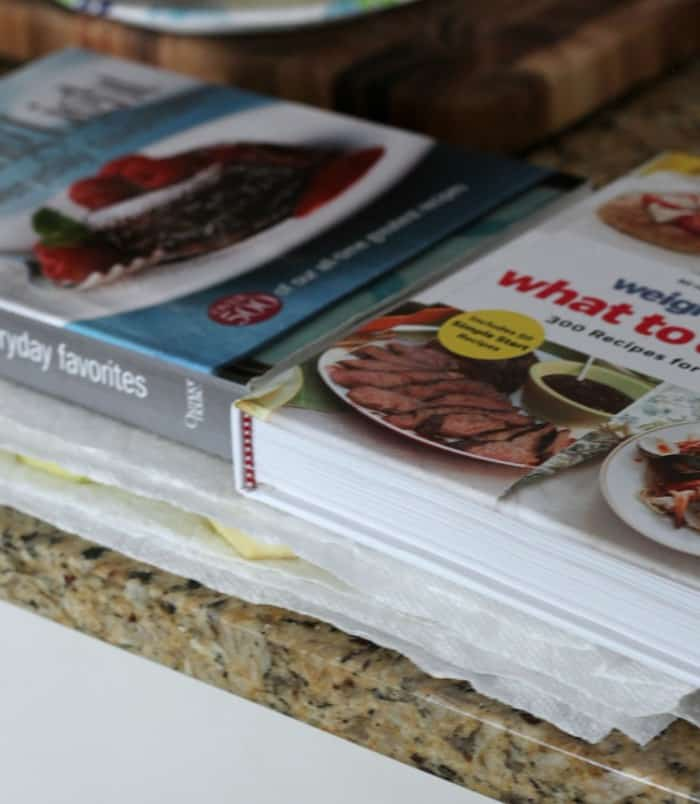 Eggplant slices layered between paper towels with cookbooks pressed on top to release moisture.