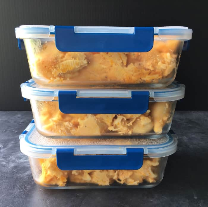 Shredded buffalo mac and cheese in glass meal prep containers.