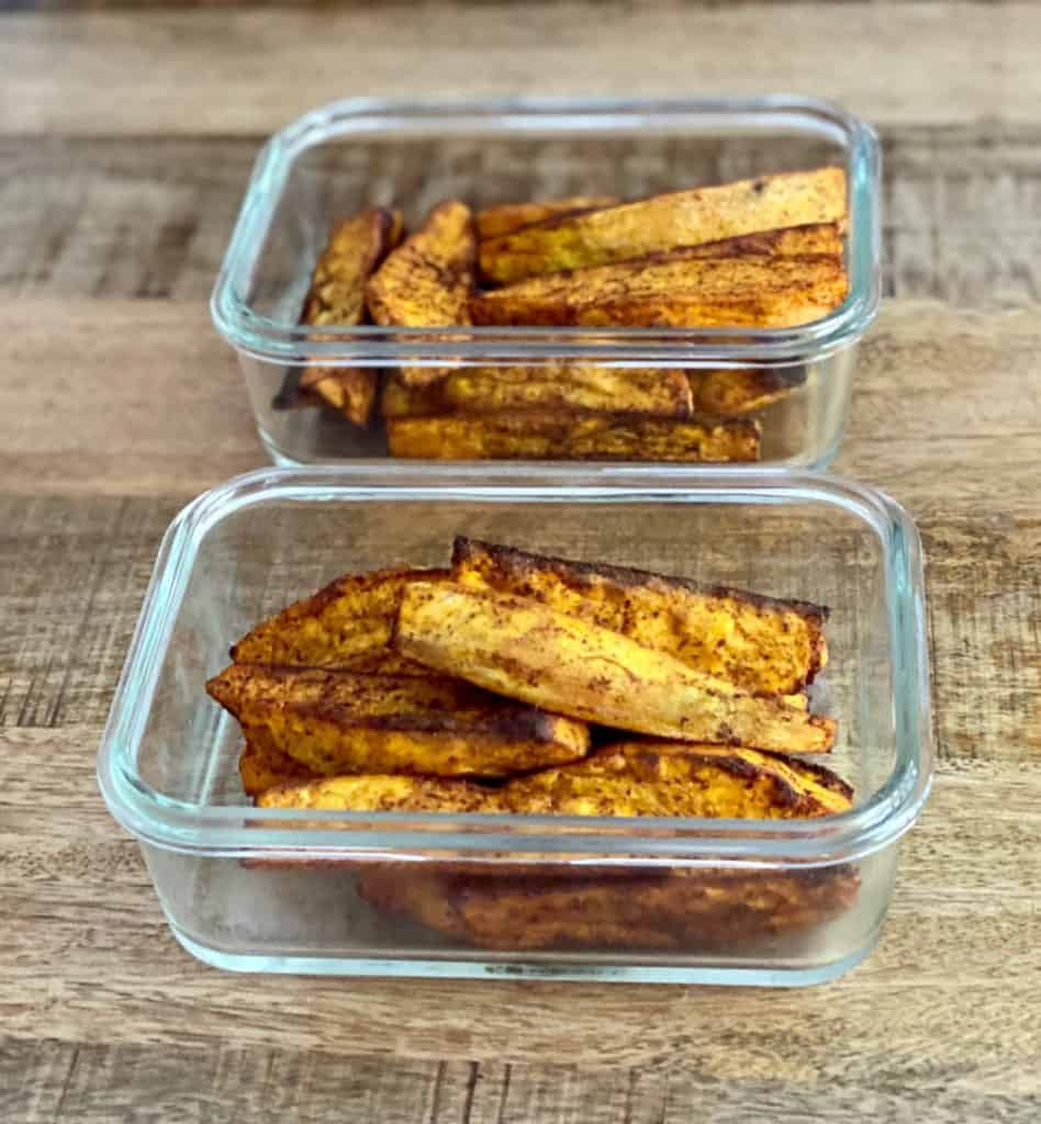 Sweet potato wedges in glass containers for meal prep.