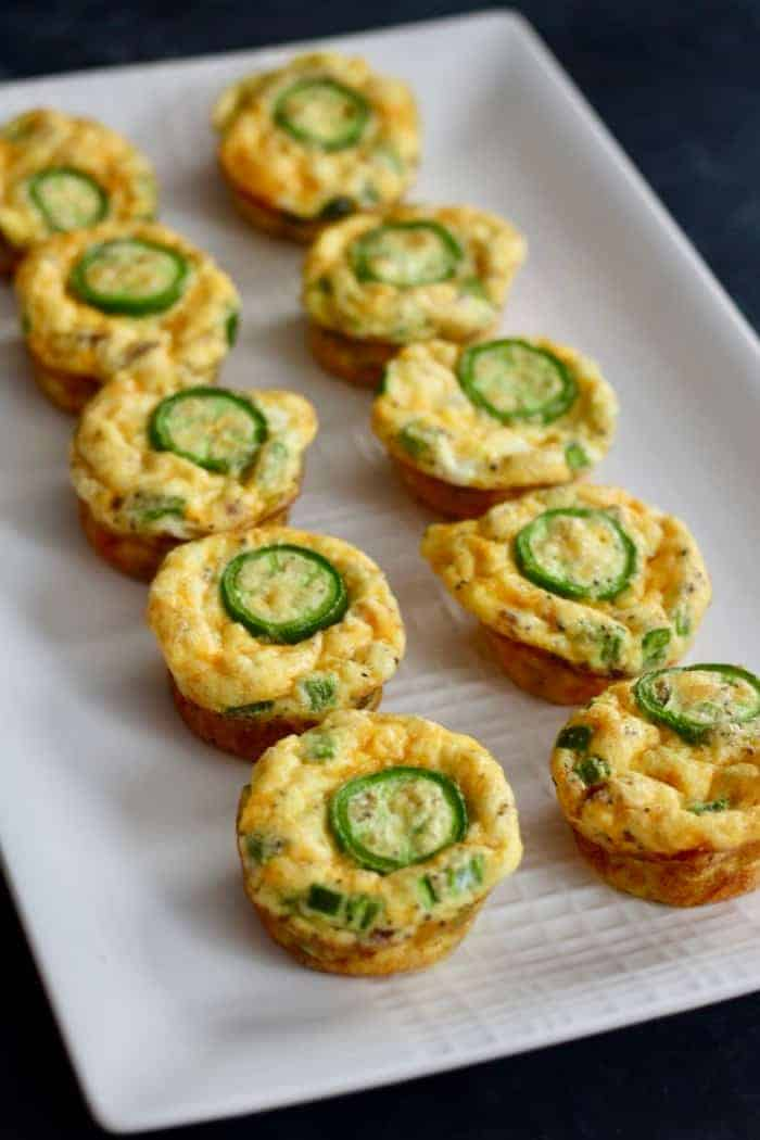 Baked low carb egg bites with cheddar, jalapeno and bacon lined on a white serving dish.