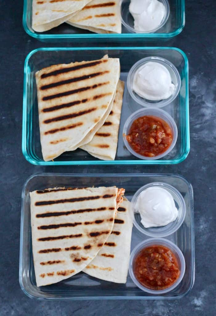 Easy meal prep for the week is shown with a row of grilled quesadillas in glass containers.