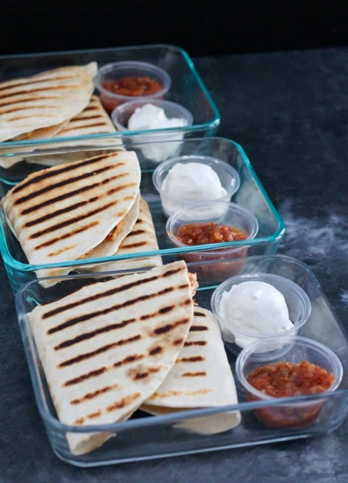 Quesadillas with containers of salsa and sour cream are an easy quick meal prep idea.