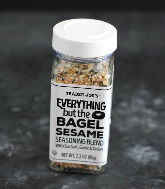 A jar of Everything But The Bagel seasoning with a gray background.