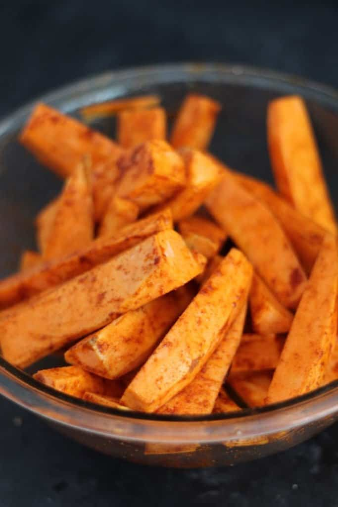 Chili-spiced roasted sweet potatoes cut into a wedge shape in a glass bowl.