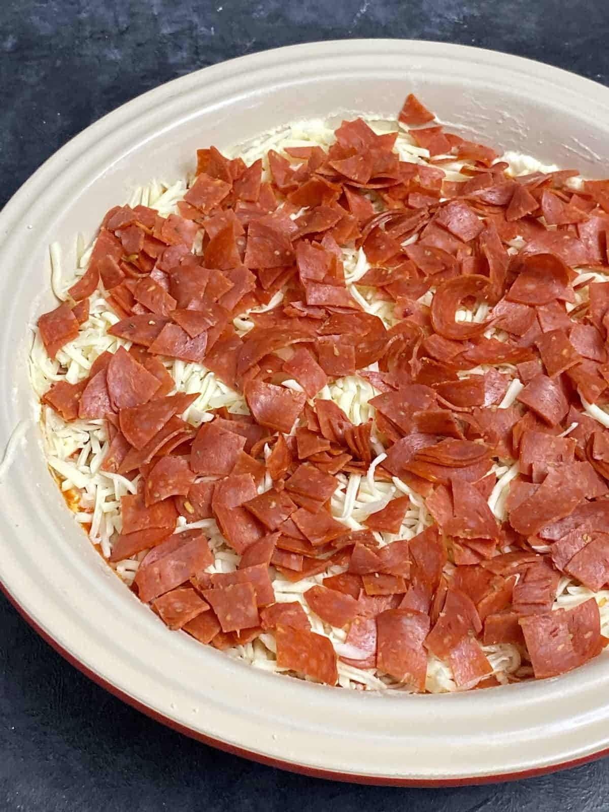 Pepperoni dip in a baking dish prior to going into the oven.