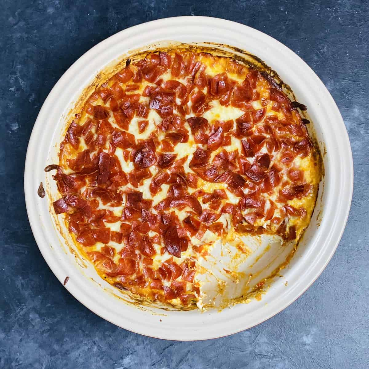 Baked pizza dip recipe with a chunk missing that's been spooned out.