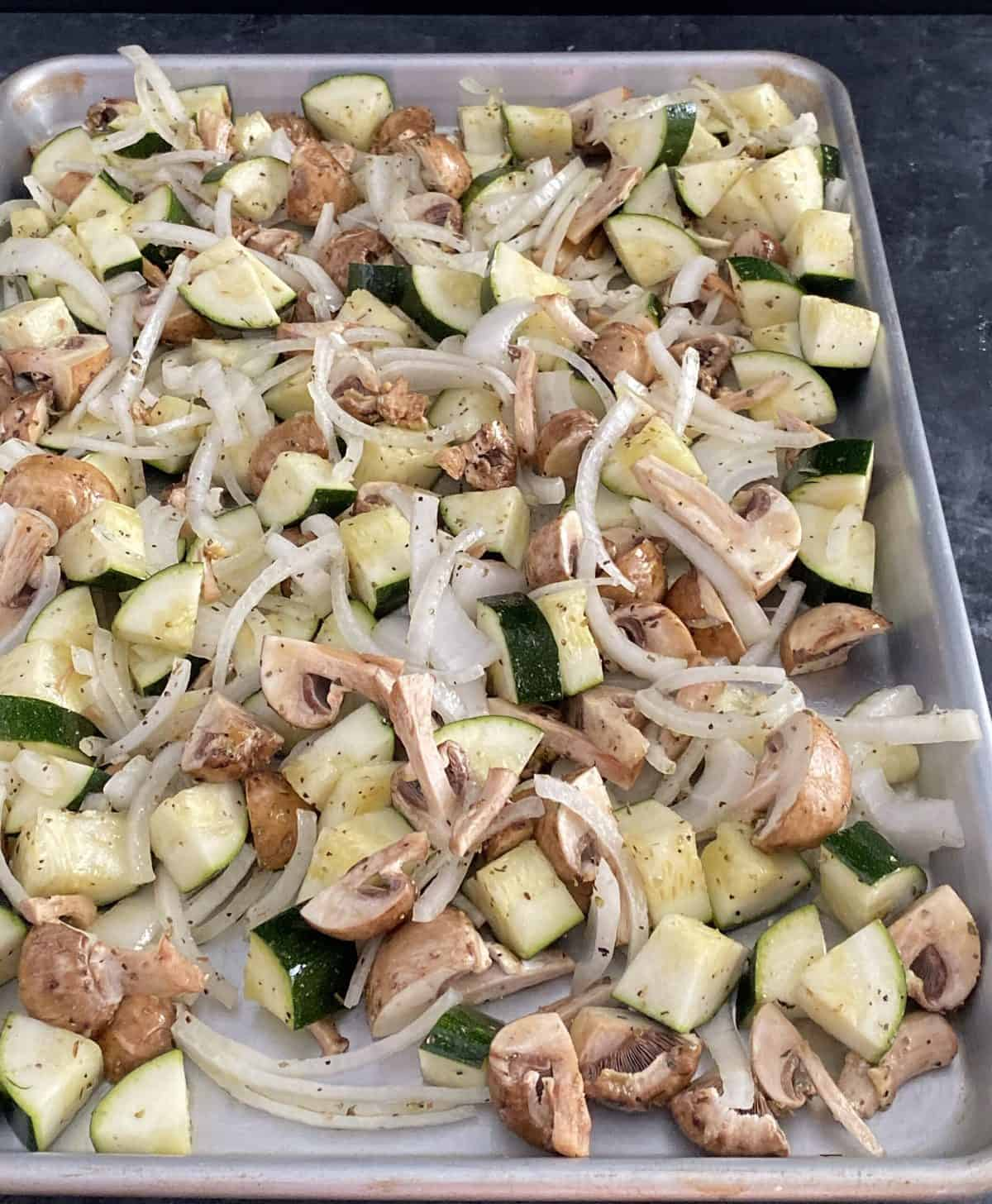 Chopped onion, mushroom, and zucchini on a roasting pan.