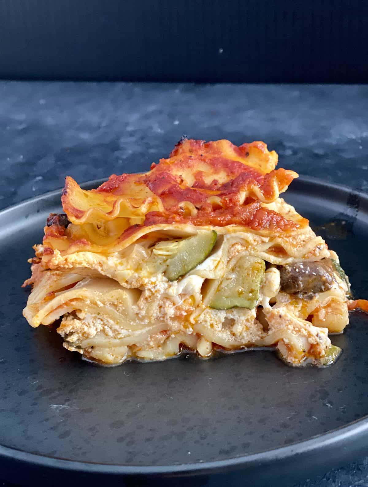 A slice of zucchini lasagna on a navy plate.