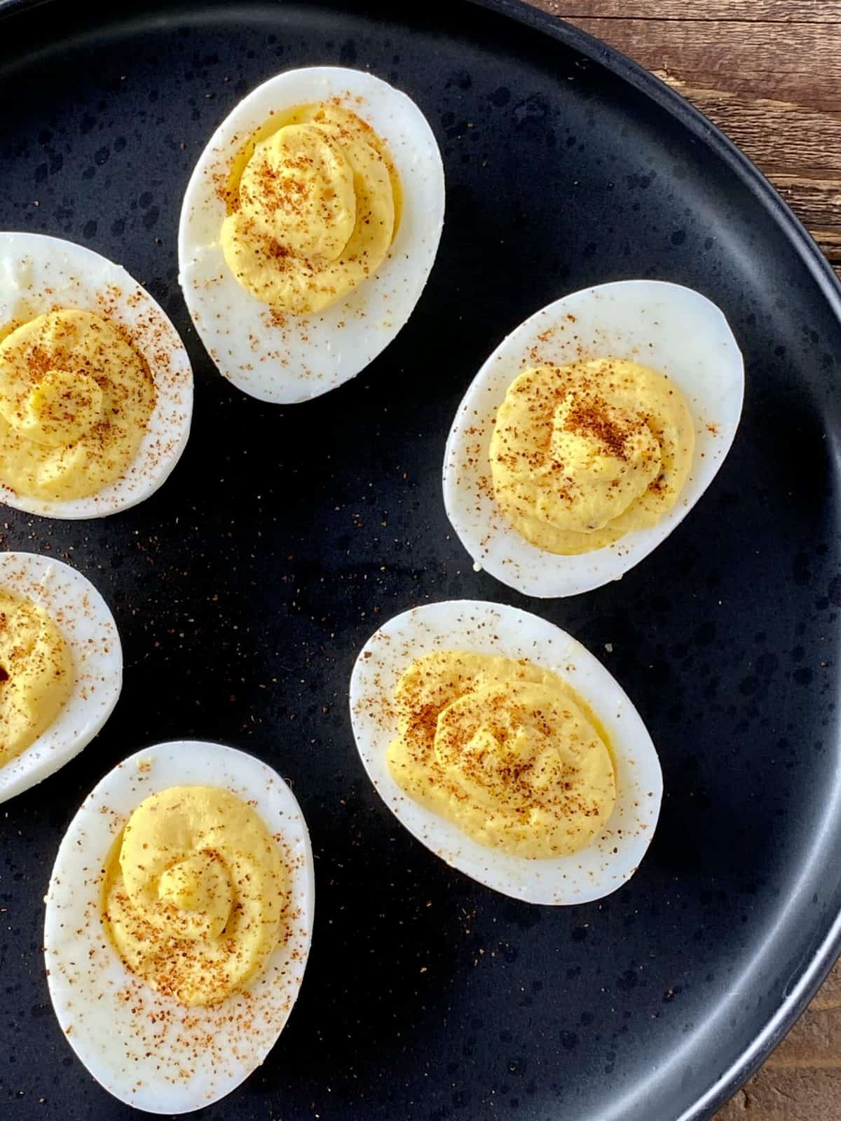 healthy deviled eggs with horseradish on a black plate