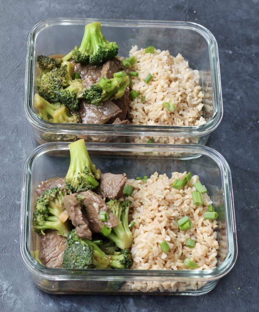Individual glass container with brown rice and beef and broccoli stir fry.
