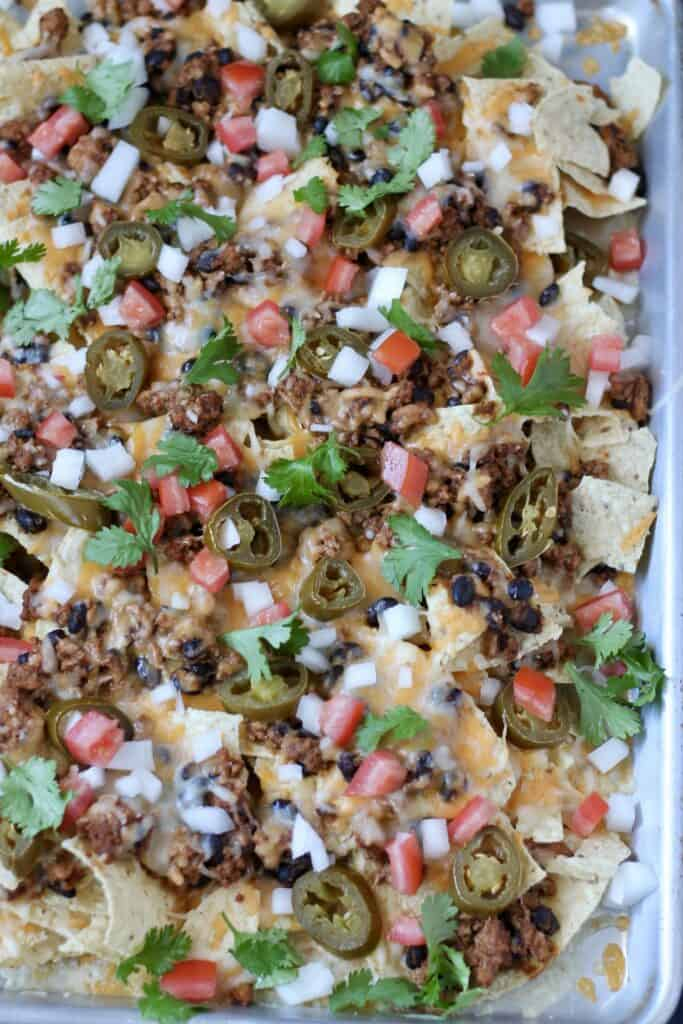 close up of ground turkey nachos freshly made on a baking dish