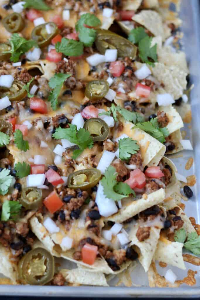 Close up of ground turkey nachos with toppings.