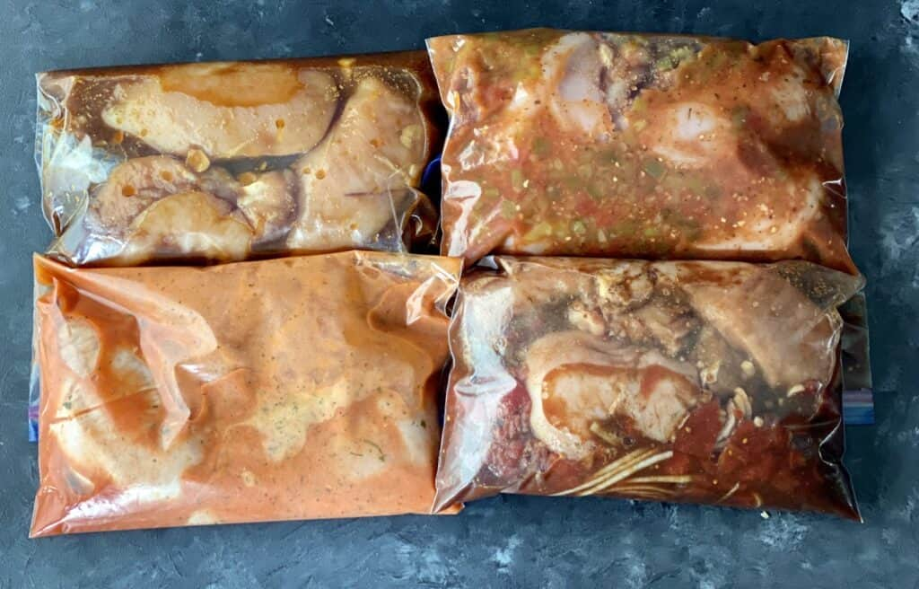 Four different chicken breast recipes with marinade in ziploc bags prior to freezing.