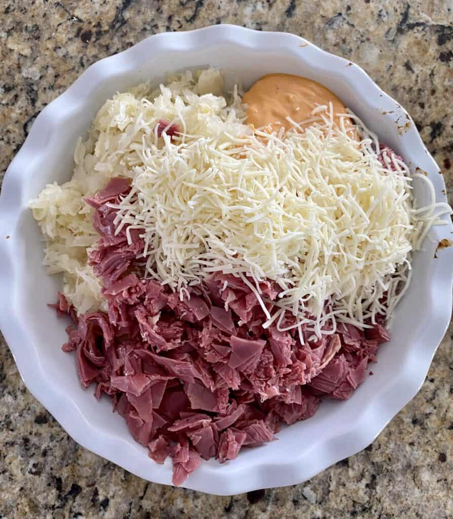 Ingredients for a rueben dip prior to baking such as corned beef, cheese, thousand island and sauerkraut