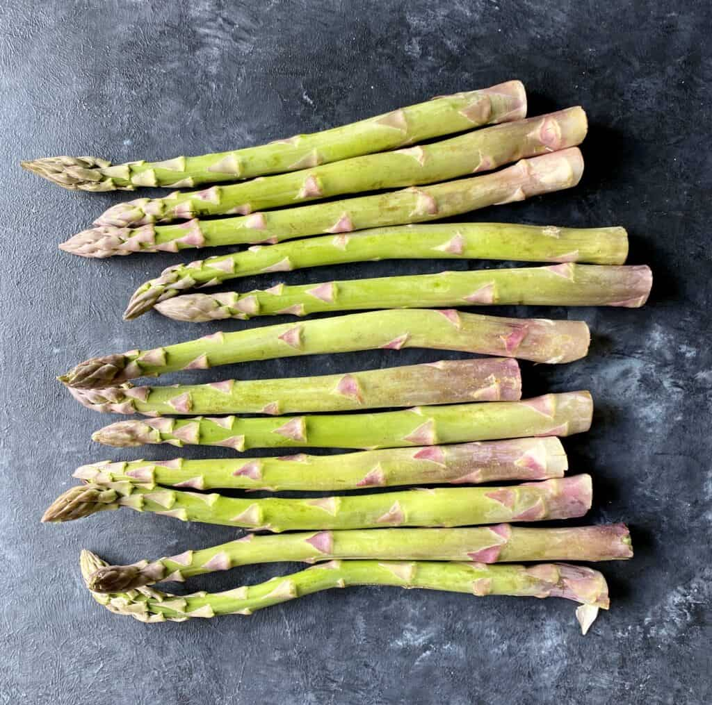 raw asparagus on dark gray table