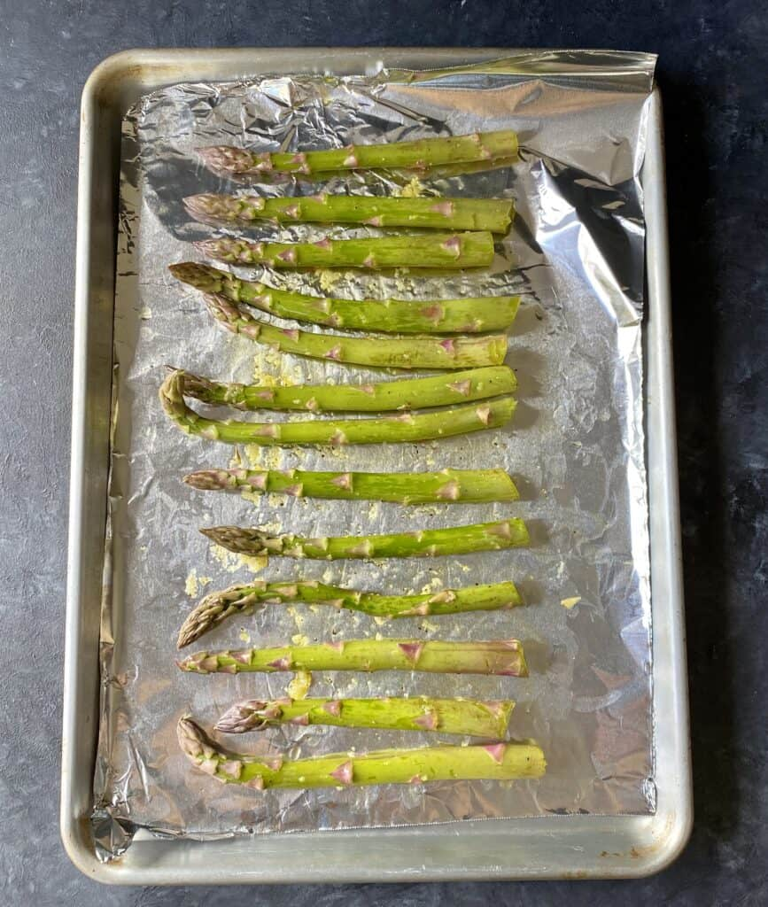 seasoned asparagus on foiled pan