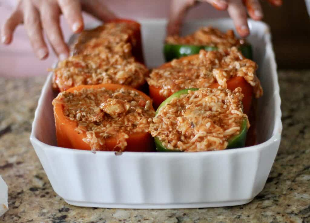 Italian stuffed peppers with filling and cheese in a baking dish