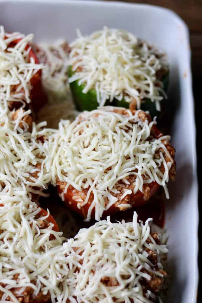 Bell peppers in a baking dish with shredded cheese on top