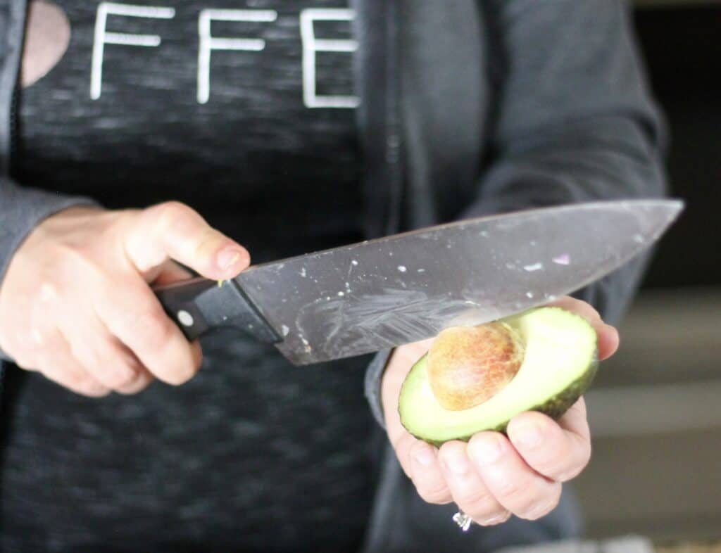 Woman demonstrating how to remove an avocado pit with a knife