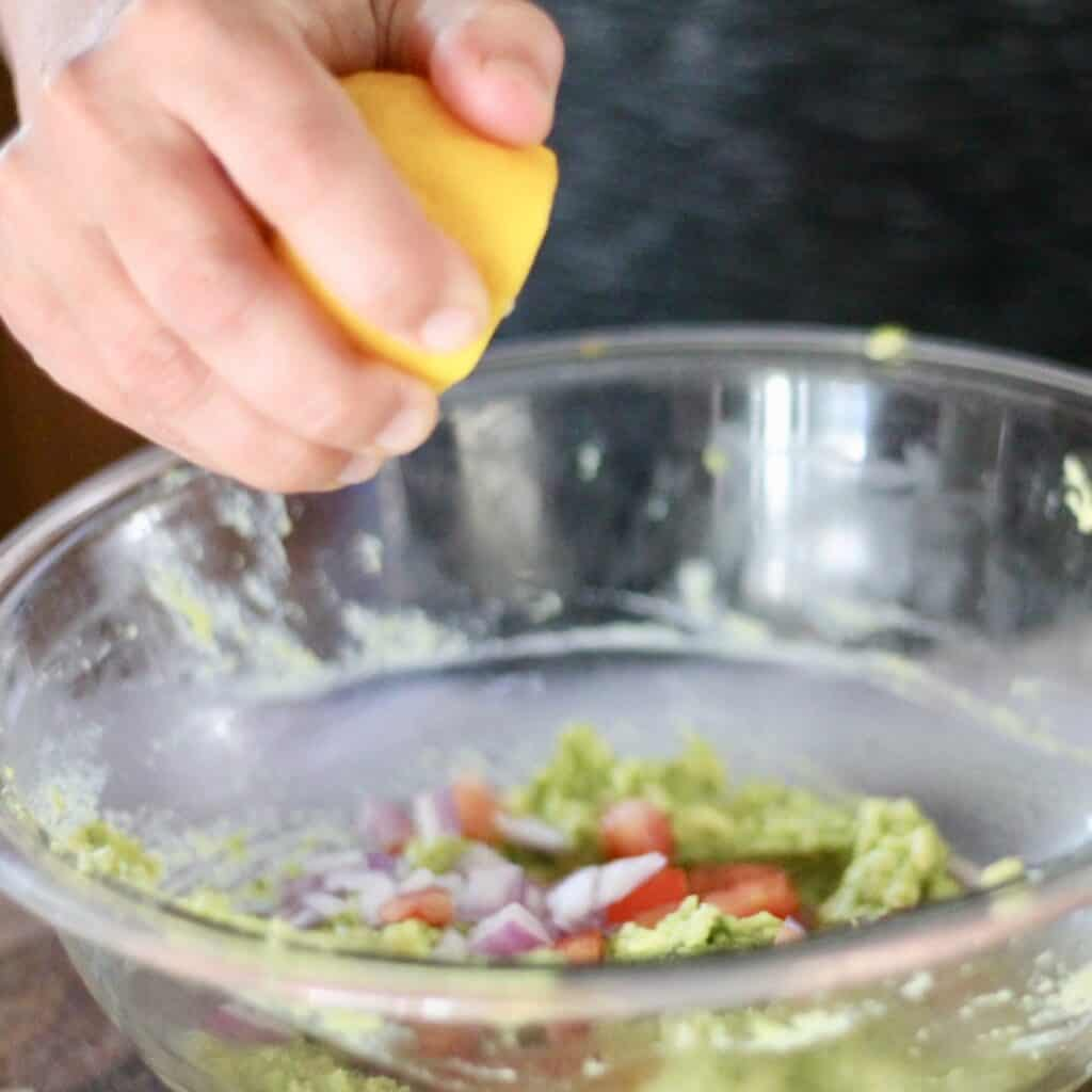 Woman squeezing lemon into a bowl of avocado, tomatoes and onions.
