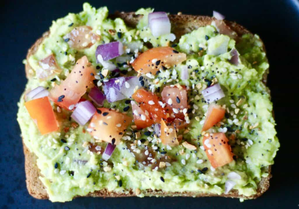 The best avocado toast, layered with mashed avocado, chunks of tomato and onion, and everything but the bagel seasoning