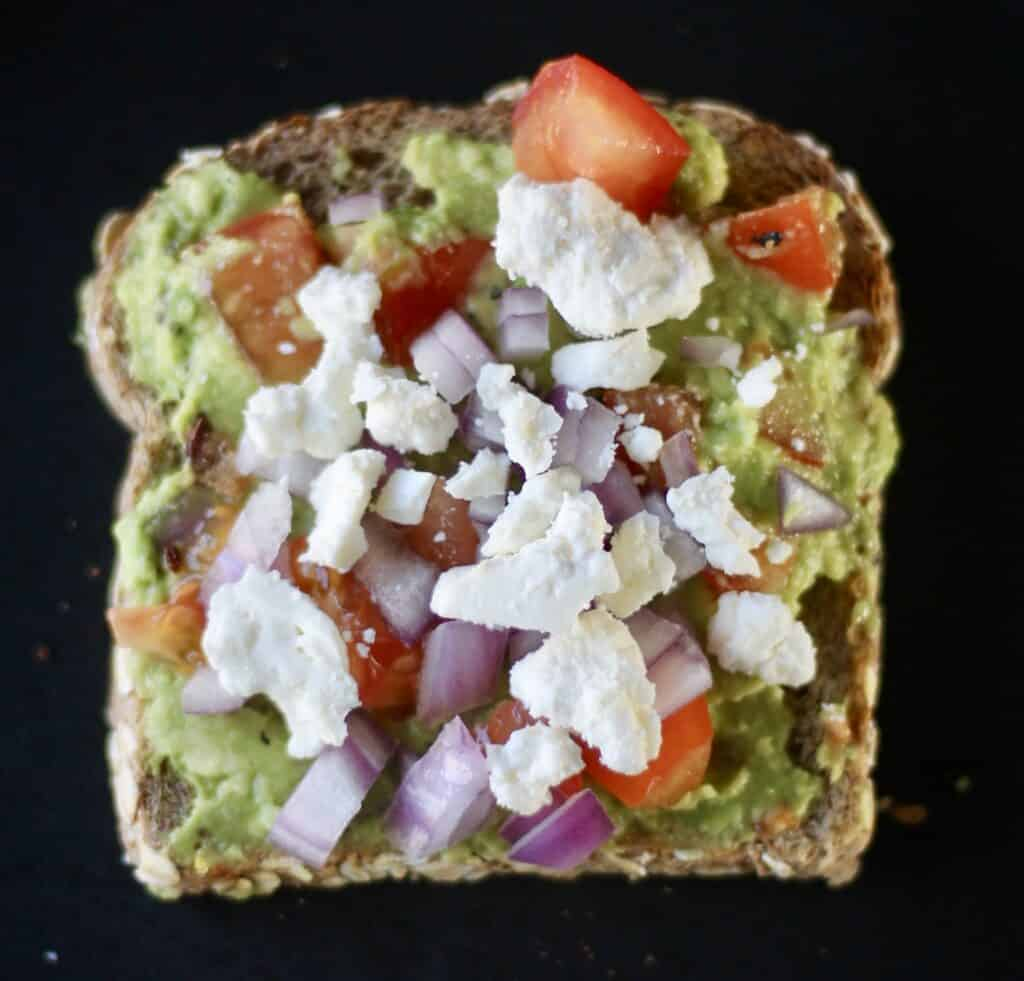 The best avocado toast - mashed avocado with chopped red tomatoes, onions, and feta