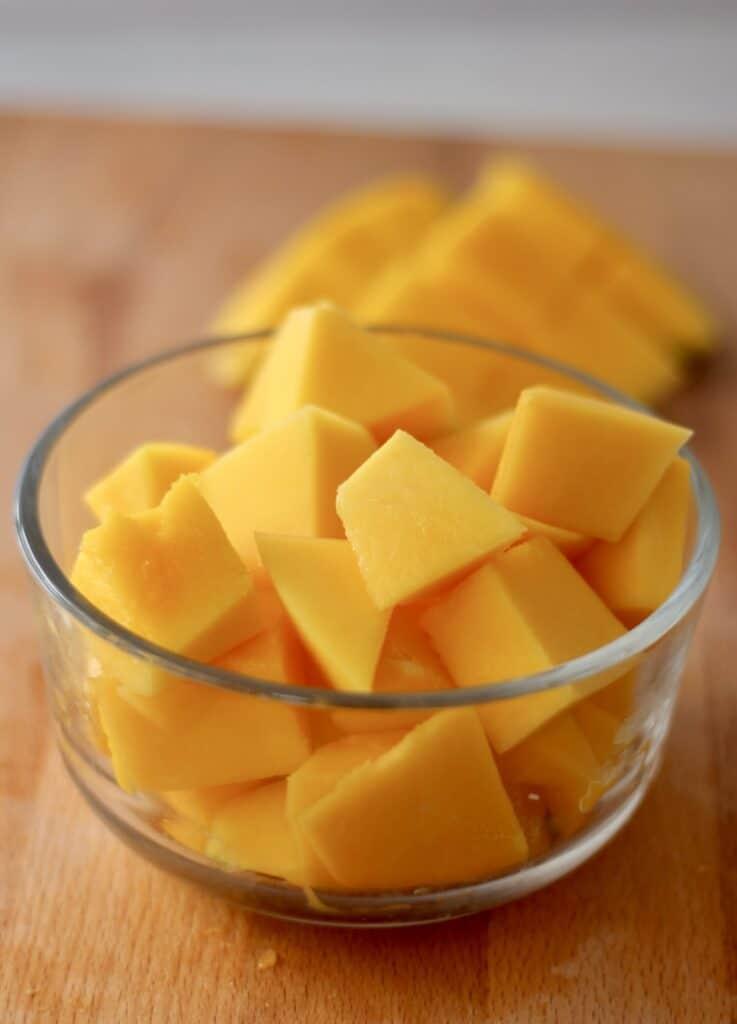 Chunks of freshly cut mango in a glass bowl.