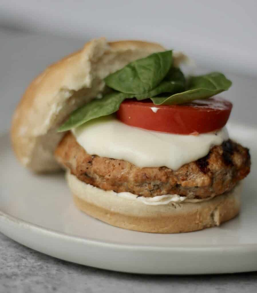 italian turkey burger on a bun with mayo, mozzarella, tomato, and basil