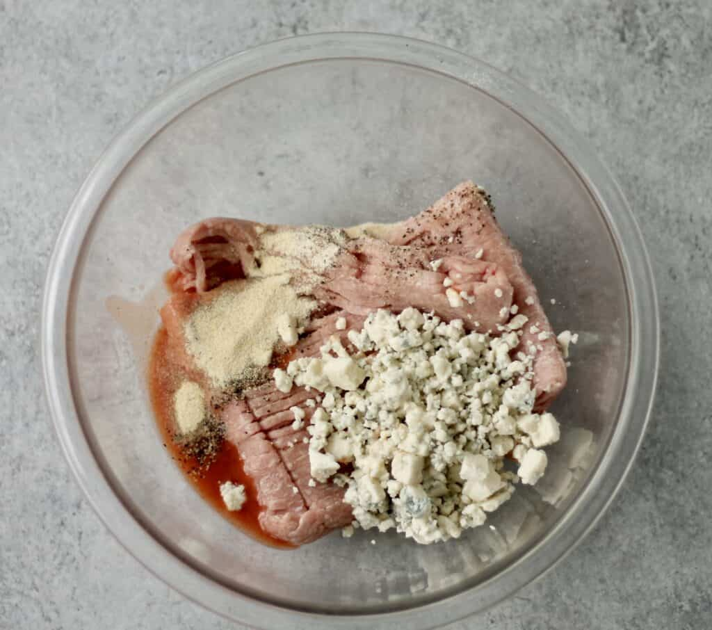 Ingredients for a buffalo turkey burget in a glass bowl - blue cheese, seasoning, ground turkey and hot sauce