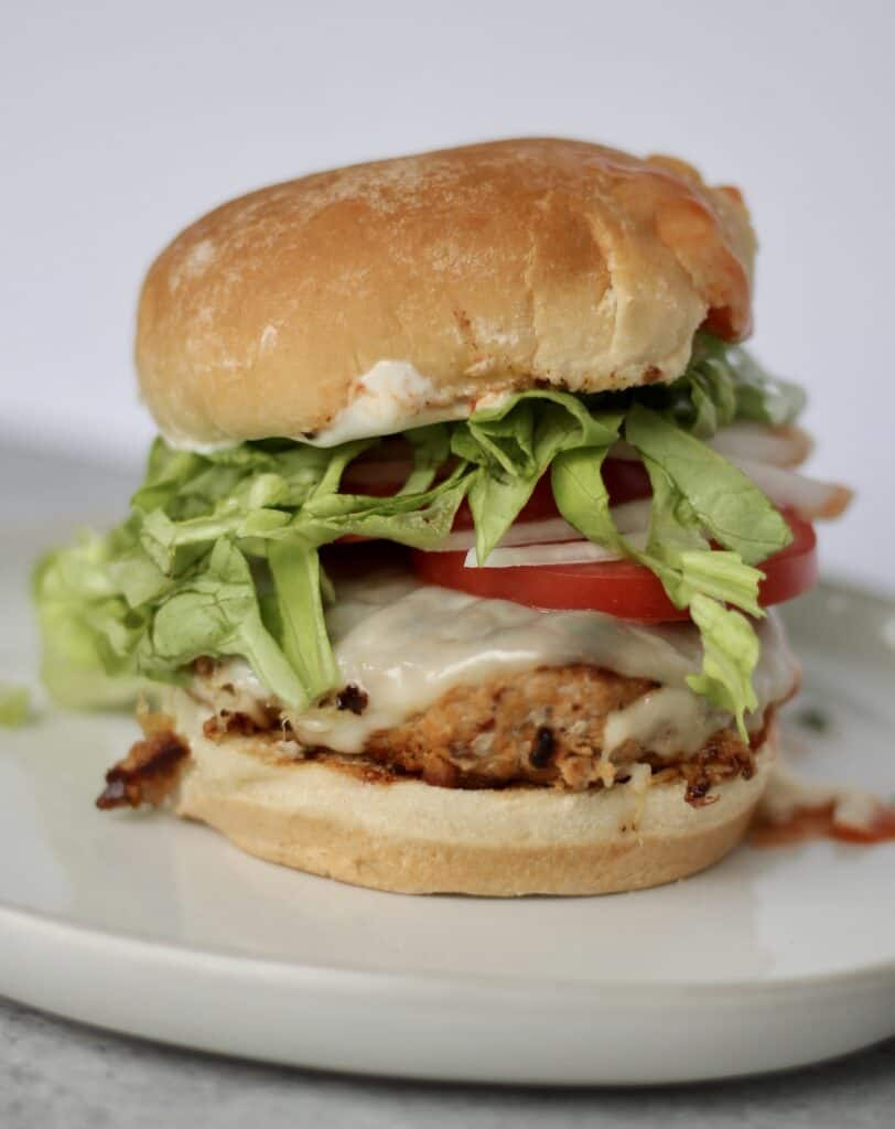 Blue cheese buffalo turkey burger piled with tomato, lettuce, and cheese.