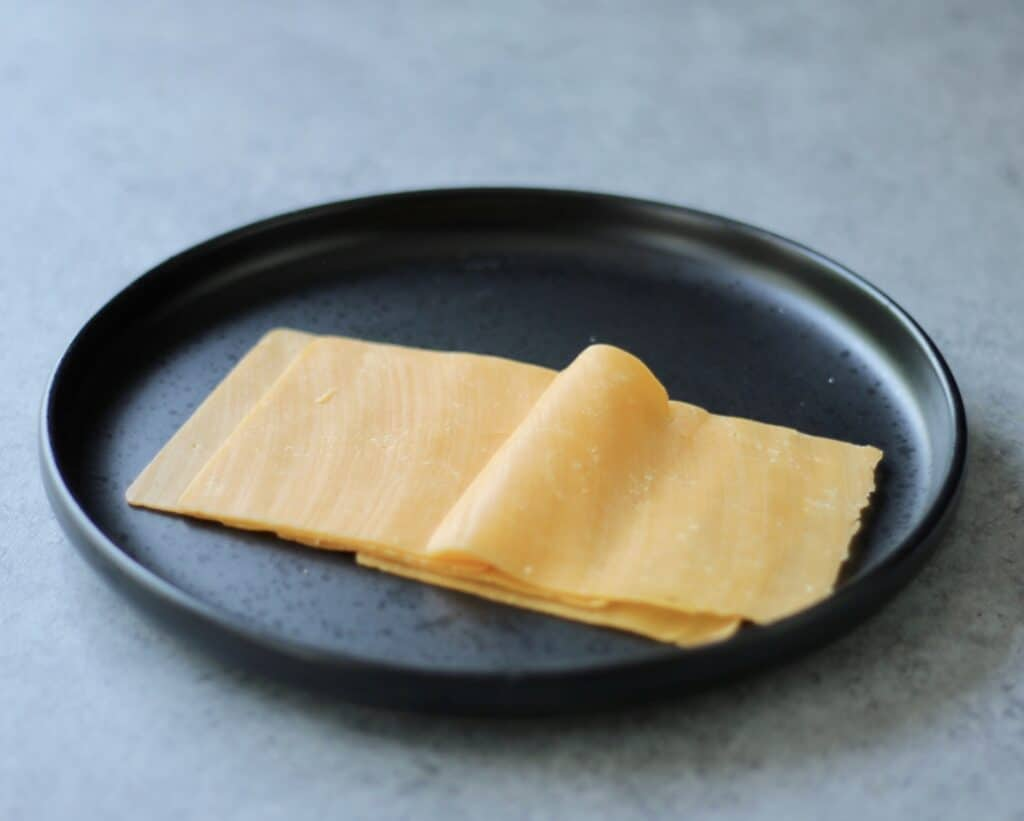 Thinly sliced cheddar cheese on a black plate