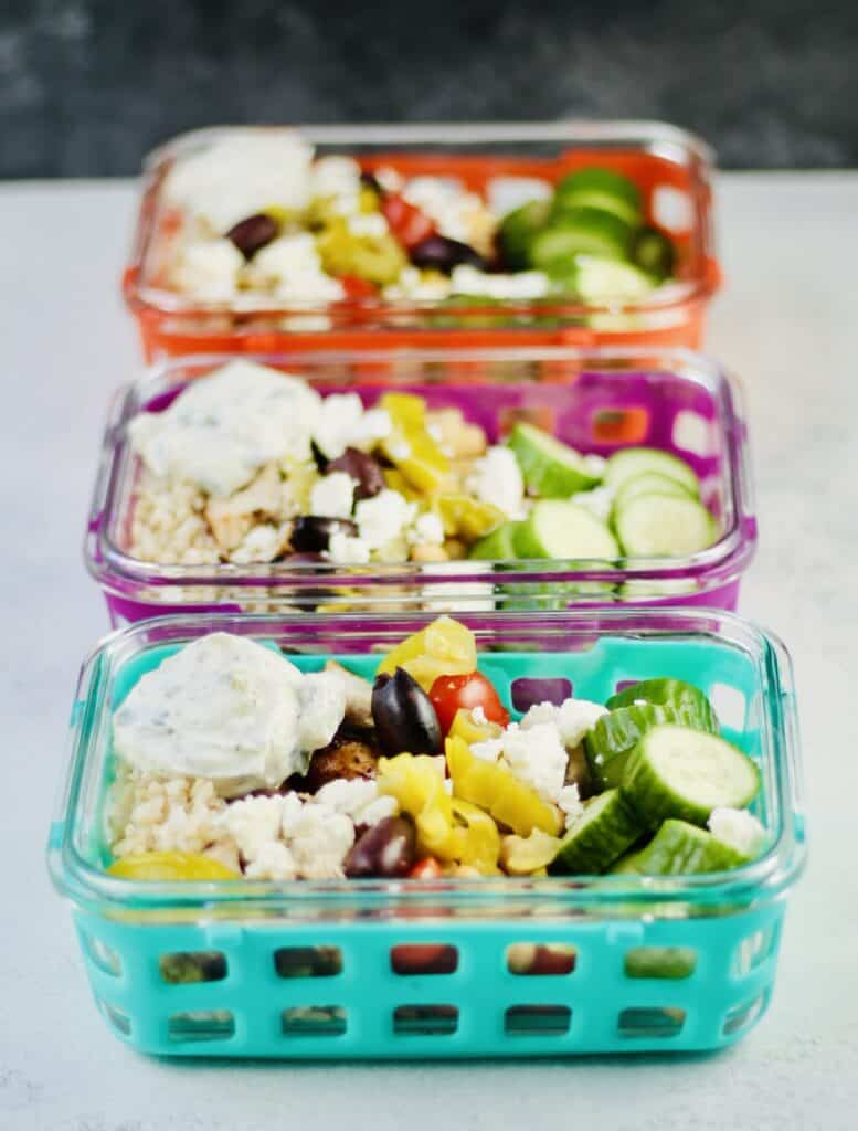 Greek chicken with rice, banana peppers, cucumbers and olives in glass containers.