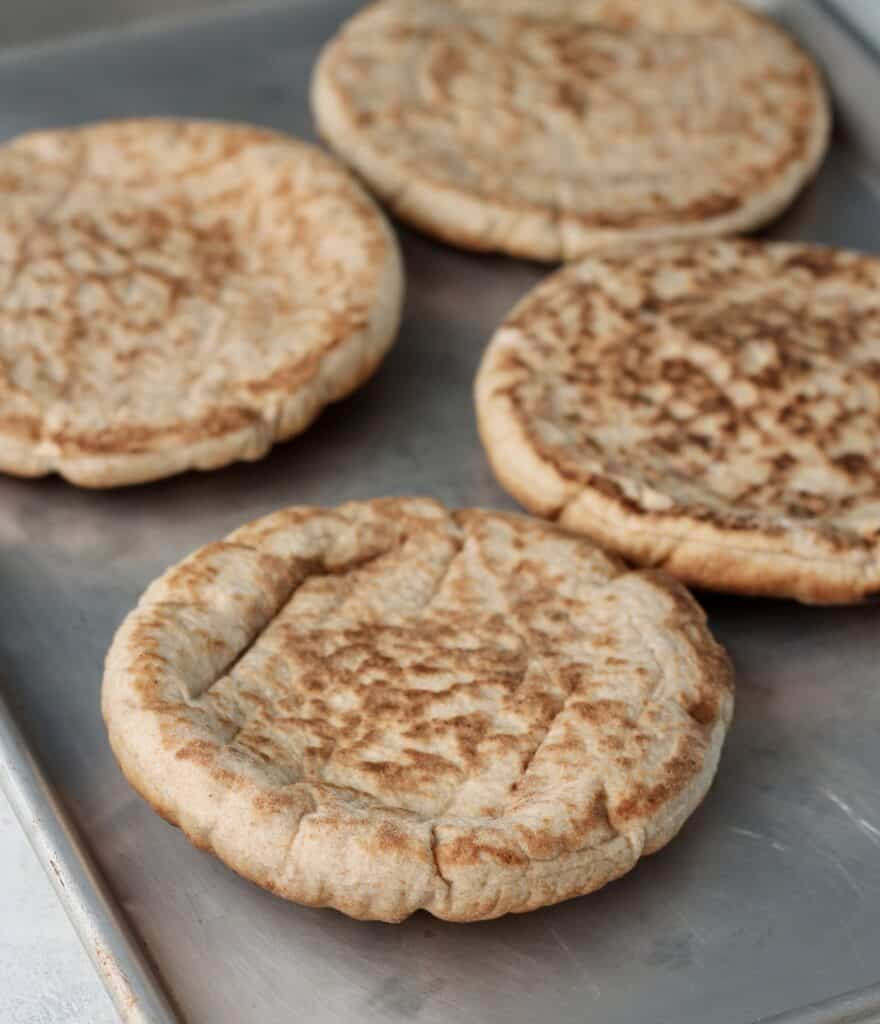 pita bread laid flat on sheet pan