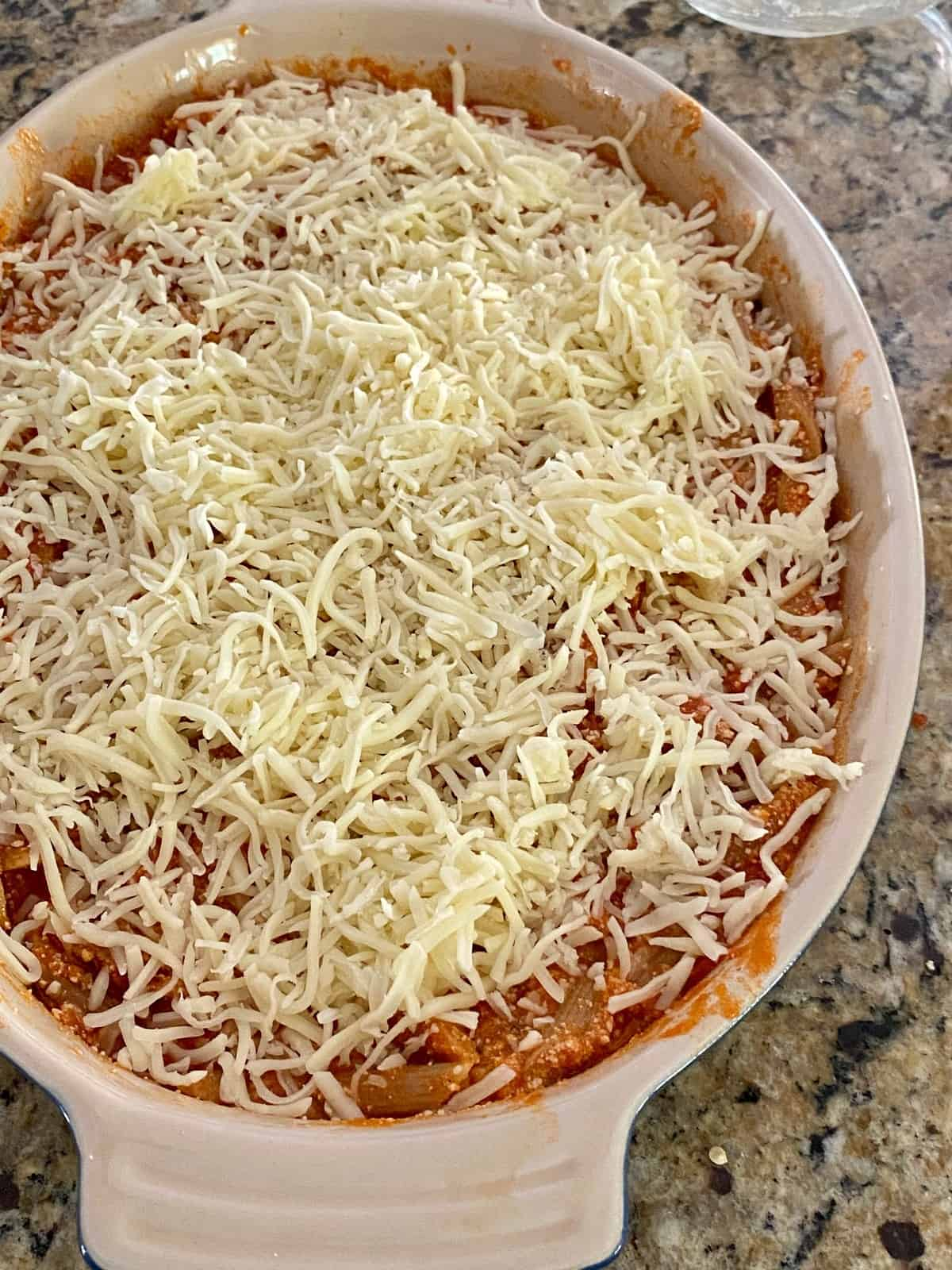 italian pasta casserole topped with cheese before baking