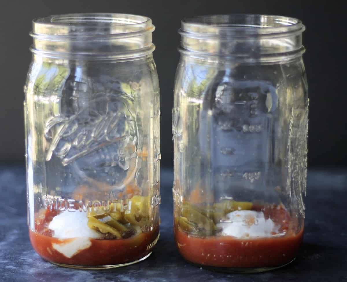 adding salsa, pickled jalapenos and vegan sour cream to mason jars