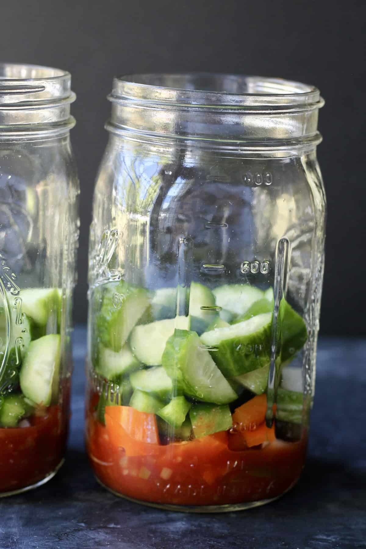 adding cucumbers to mason jar salad