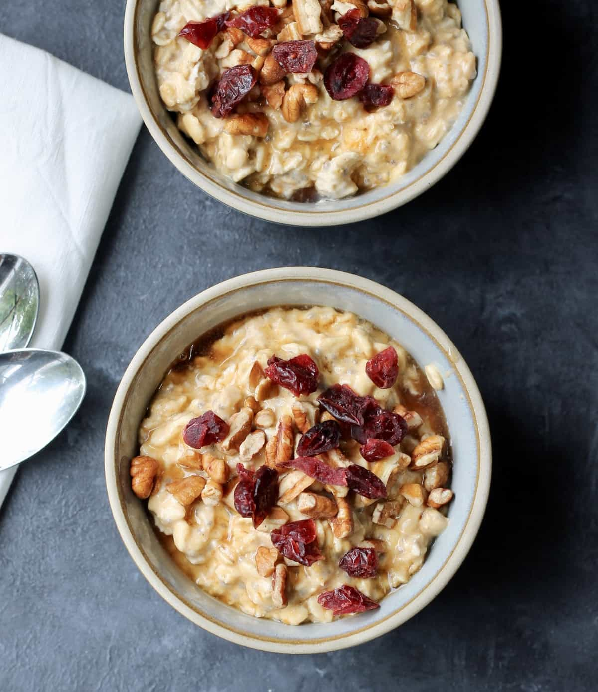 pumpkin overnights oats in a bowl topped with pecans and cranberries