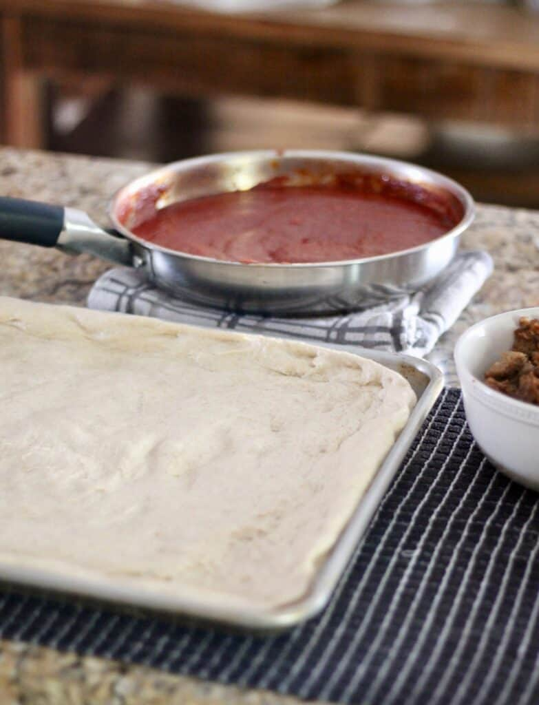 Pizza dough on a sheet pan with homemade pizza sauce in the background