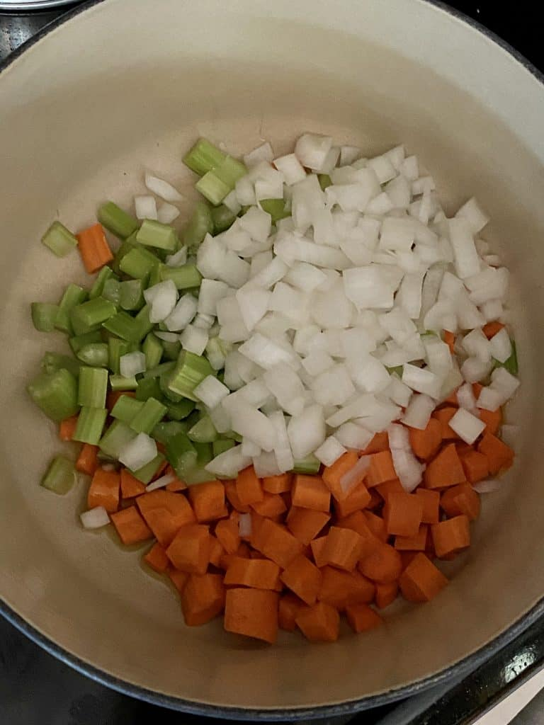 carrots, celery, and onion in a pot for cheeseburger soup