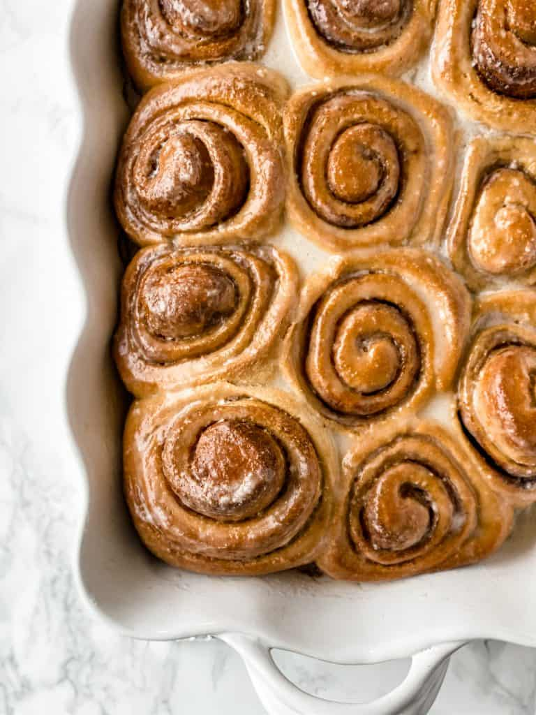 cooked sweet rolls in a white ceramic pan