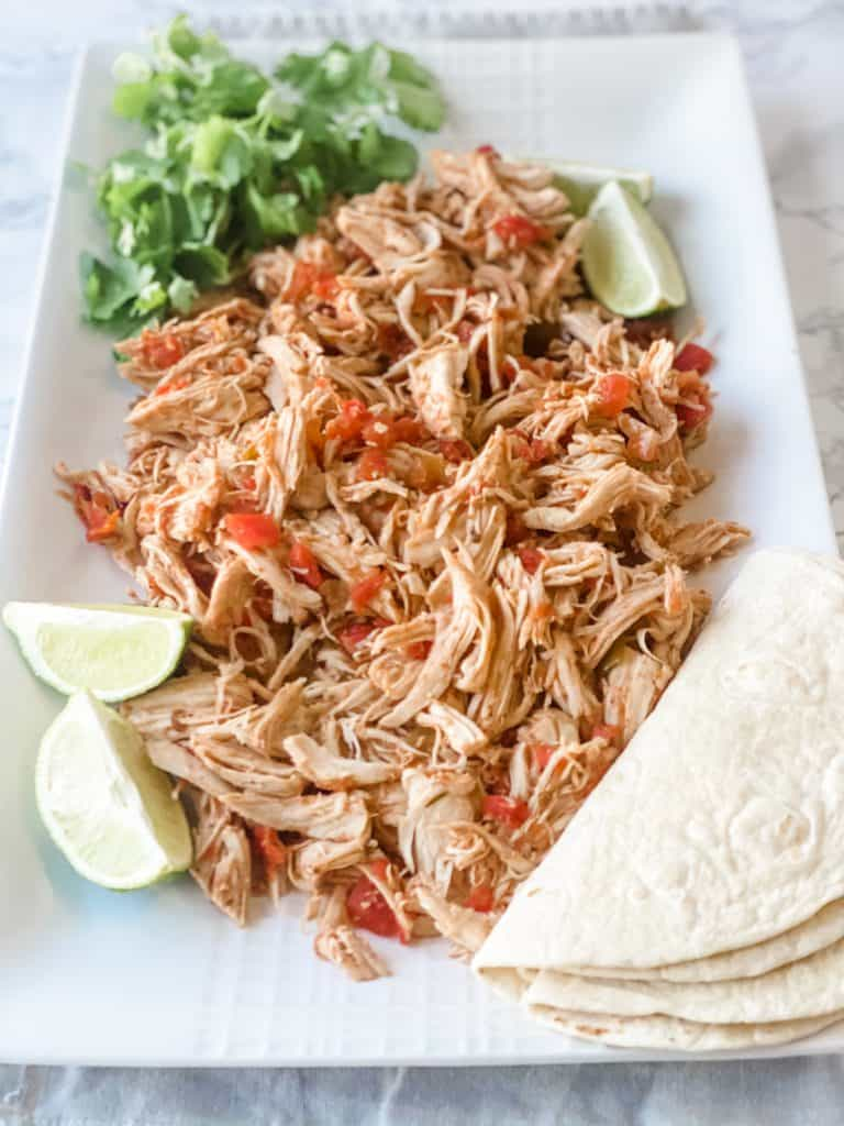 Slow cooker salsa chicken shredded on a platter with tortillas and lime