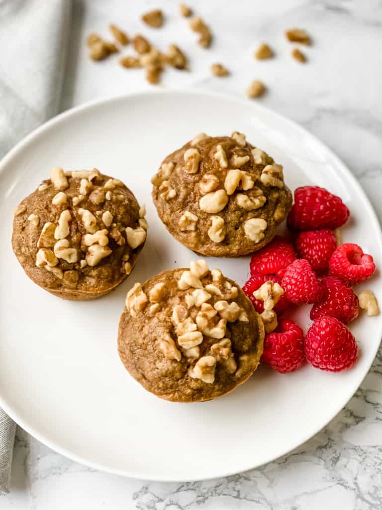 three banana nut muffins on a plate with raspberries