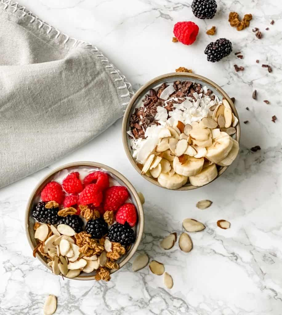Two yogurt bowls. one is topped with berries, nuts and granola. The other is topped with bananas, coconut, and cocoa nibs.