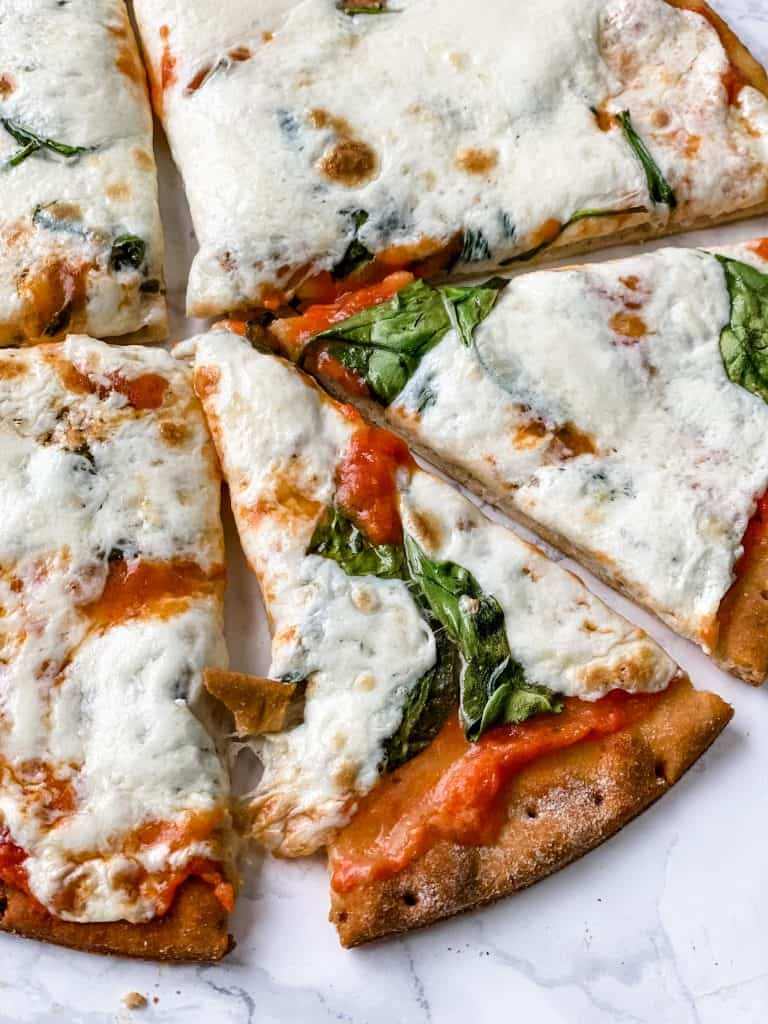 Keto pizza sauce on cauliflower pizza crust with cheese and spinach