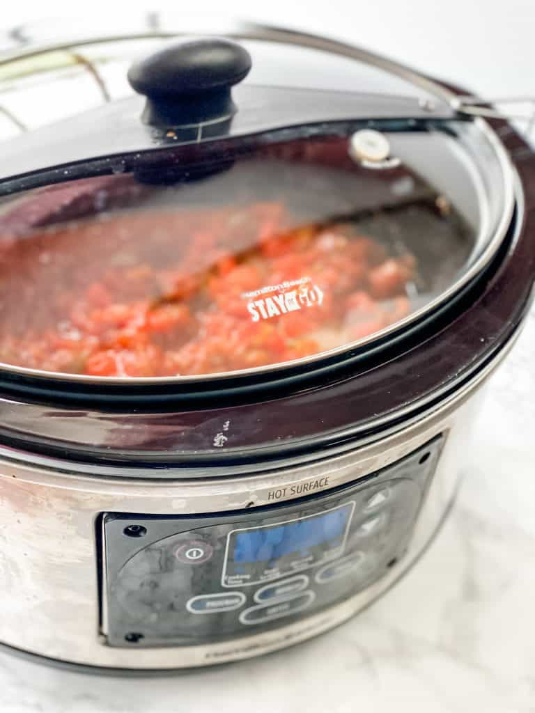 slow cooker with salsa and chicken inside