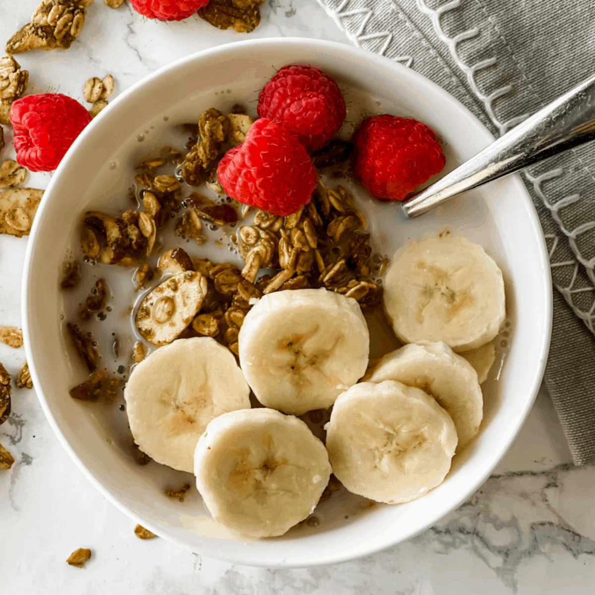 granola in a bowl with milk and bananas