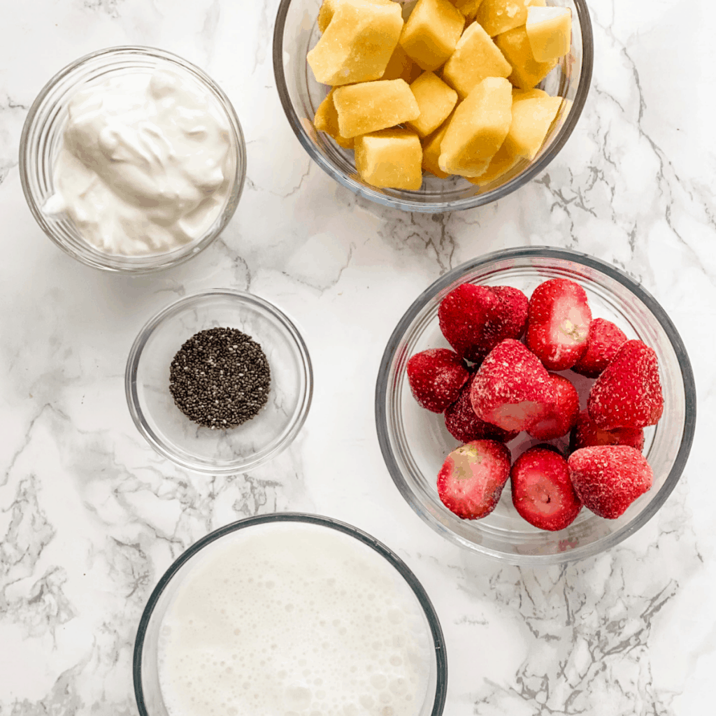 Ingredients to make a strawberry and mango smoothie