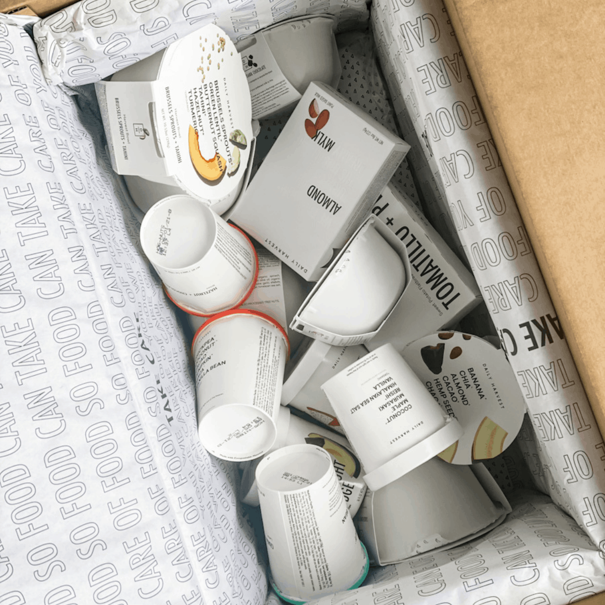 a box filled with a variety of food items from daily harvest.