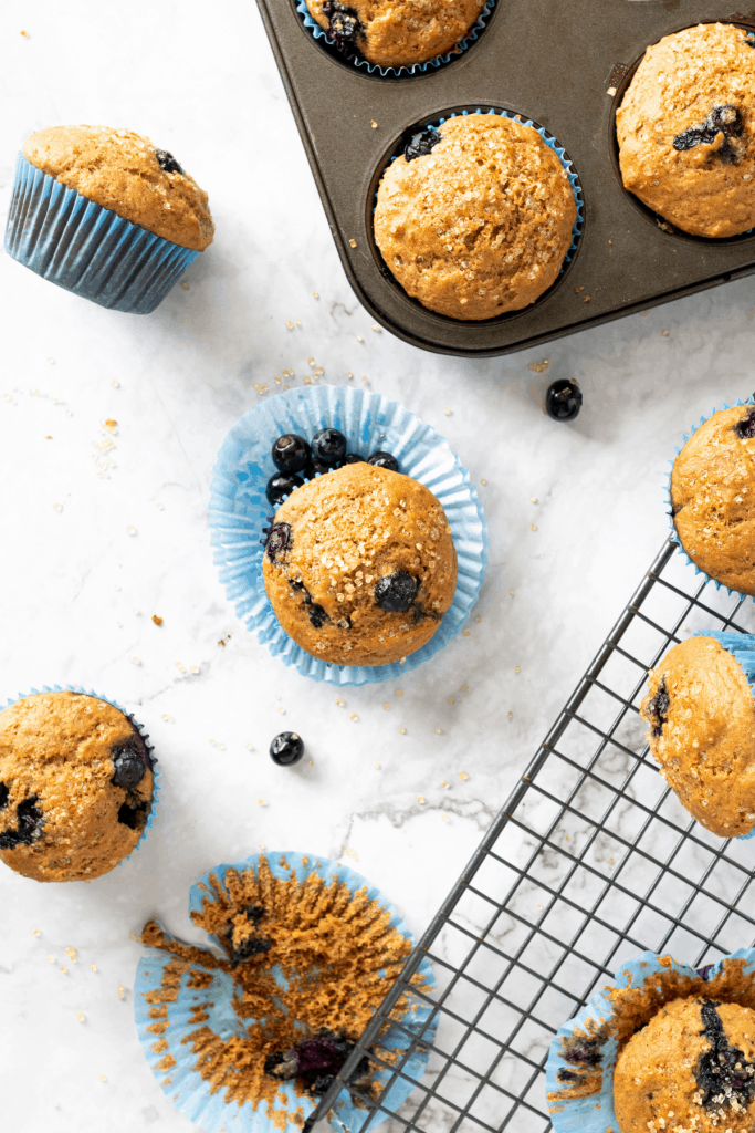 healthy blueberry Greek yogurt muffins in a pan and on a wire cooling rack.
